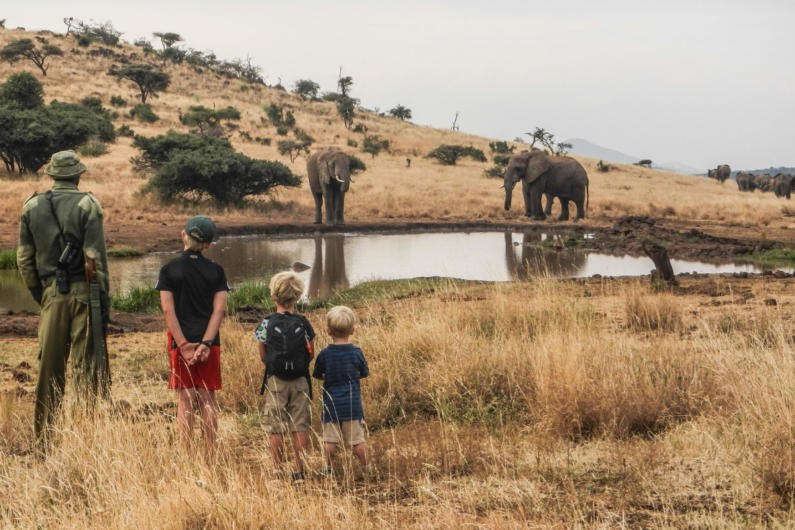 Children watching elephant on foot